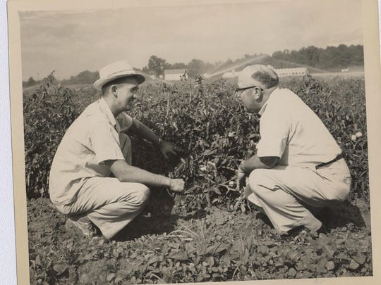 An archival photo documents an agent offering advice to a farmer.