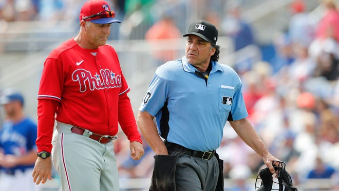FILE - In this March 8, 2020, file photo, Philadelphia Phillies' pitching coach Bryan Price walks with umpire Phil Cuzzi during a spring training baseball game, Sunday,, in Dunedin, Fla. Price could end up being the most valuable addition the Phillies made in the offseason if he can get some talented members of the staff to reach their potential.(AP Photo/Carlos Osorio, File)
