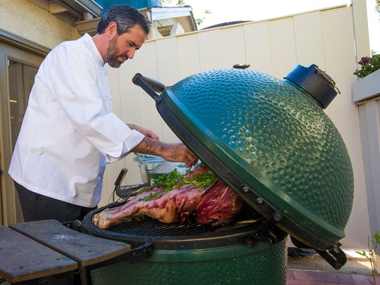 Chef Kevin Binkley seasons a lamb that he's cooking