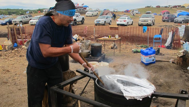 Phil Daw Sr., of Albuquerque, N.M., helps cook beef stew to feed hundreds at an encampment near North Dakota's Standing Rock Sioux reservation.