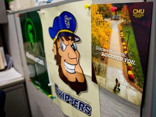 Signs for various Michigan universities are displayed in the counseling office Friday at Marysville High School.