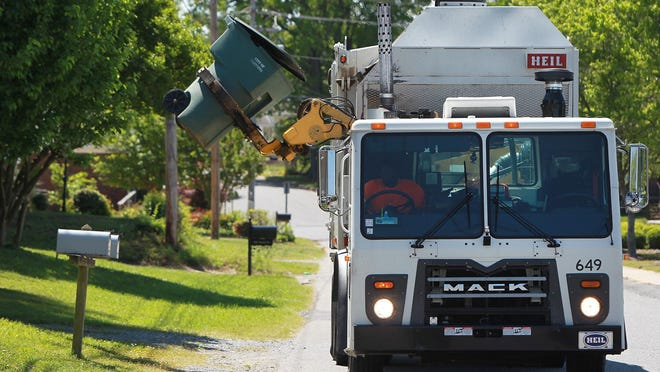 A garbage truck collects trash from trash bins in this file photo.