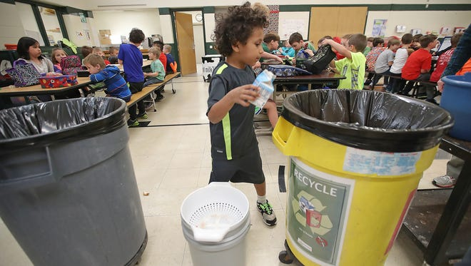Coltyn Dorner recycles his empty milk cartonafter eating lunch at Wequiock Elementary School in Green Bay.
