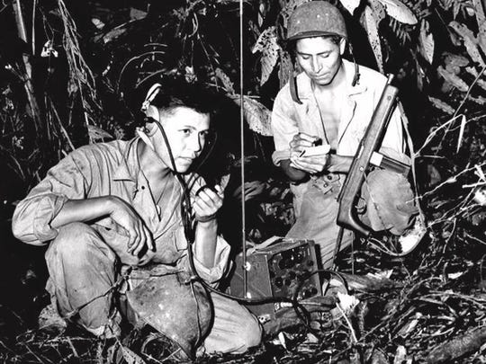 Corporal Henry Bahe, Jr., left, and Pvt. First Class George H. Kirk, Navajo code talkers serving with a Marine Signal Unit, operate a portable radio set in a jungle clearing, close behind the front lines on the island of Bougainville in New Guines, (present-day Papua New Guinea) in this December, 1943.