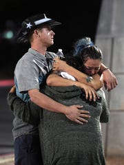 People hug and cry outside the Thomas & Mack Center.