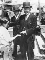 John D. Rockefeller gives a dime to a child, in this undated picture.