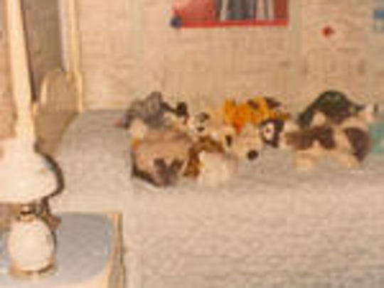 Maureen's childhood bed, loaded with stuffed animals and her pet cat.