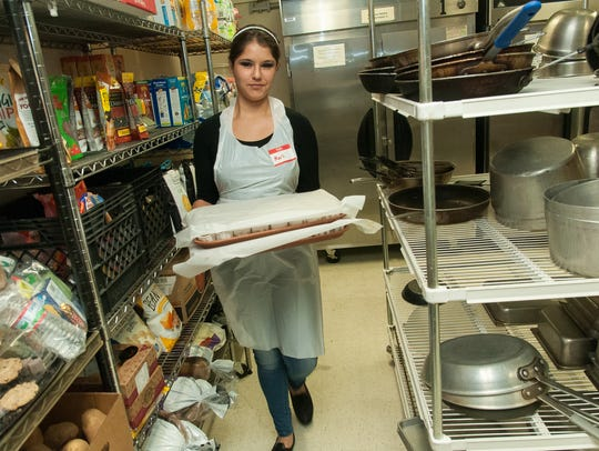 Volunteer Marli Tellez fetches a tray of green chile