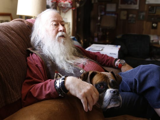 """Sherwood """"Woody"""" Moore relaxes in the living room of his Farmington home with his dog Curry."""