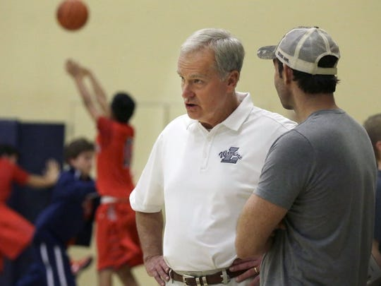 High school basketball coach Charles Freet speaks with a man during warm ups before a junior varsity basketball game in Argyle, Texas, on Friday, Feb. 10, 2017.