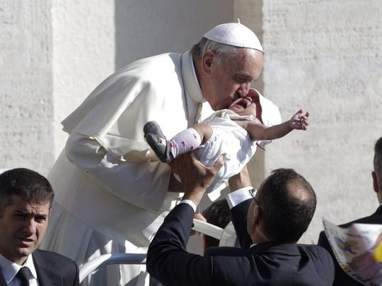 Pope Francis kisses an infant handed to him during his driven tour through the crowd in St. Peter's Square before delivering his message, translated in several languages, at his weekly general audience, at the Vatican, Wednesday, Sept. 25, 2013.