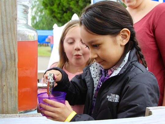 Areana Arriaga, 8, pours a glass of lemonade for a customer while Payton Bays, 8, looks on. The pair hosted a lemonade stand at the Keizer Iris Festival as part of Lemonade Day on Saturday, May 20, 2017.