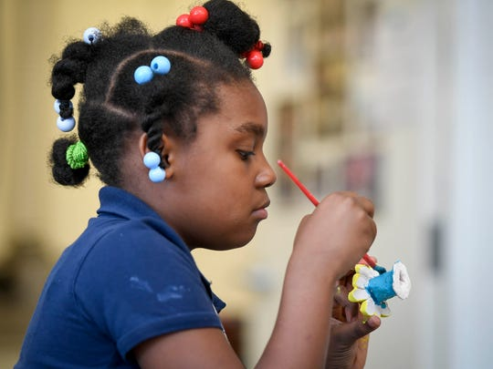 Lanayn Guthrie, 8, paints a ceramic daisy as children make garden art to be sold at Patchwork Central's pancake breakfast fundraiser Saturday.