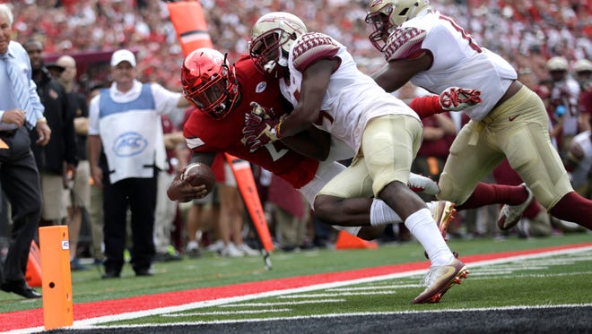 Louisville's Brandon Radcliff dives for the goal line as FSU's Tarvarus McFadden pushes him out of bounds during their game at Papa John's Cardinals Stadium in Louisville on Saturday.