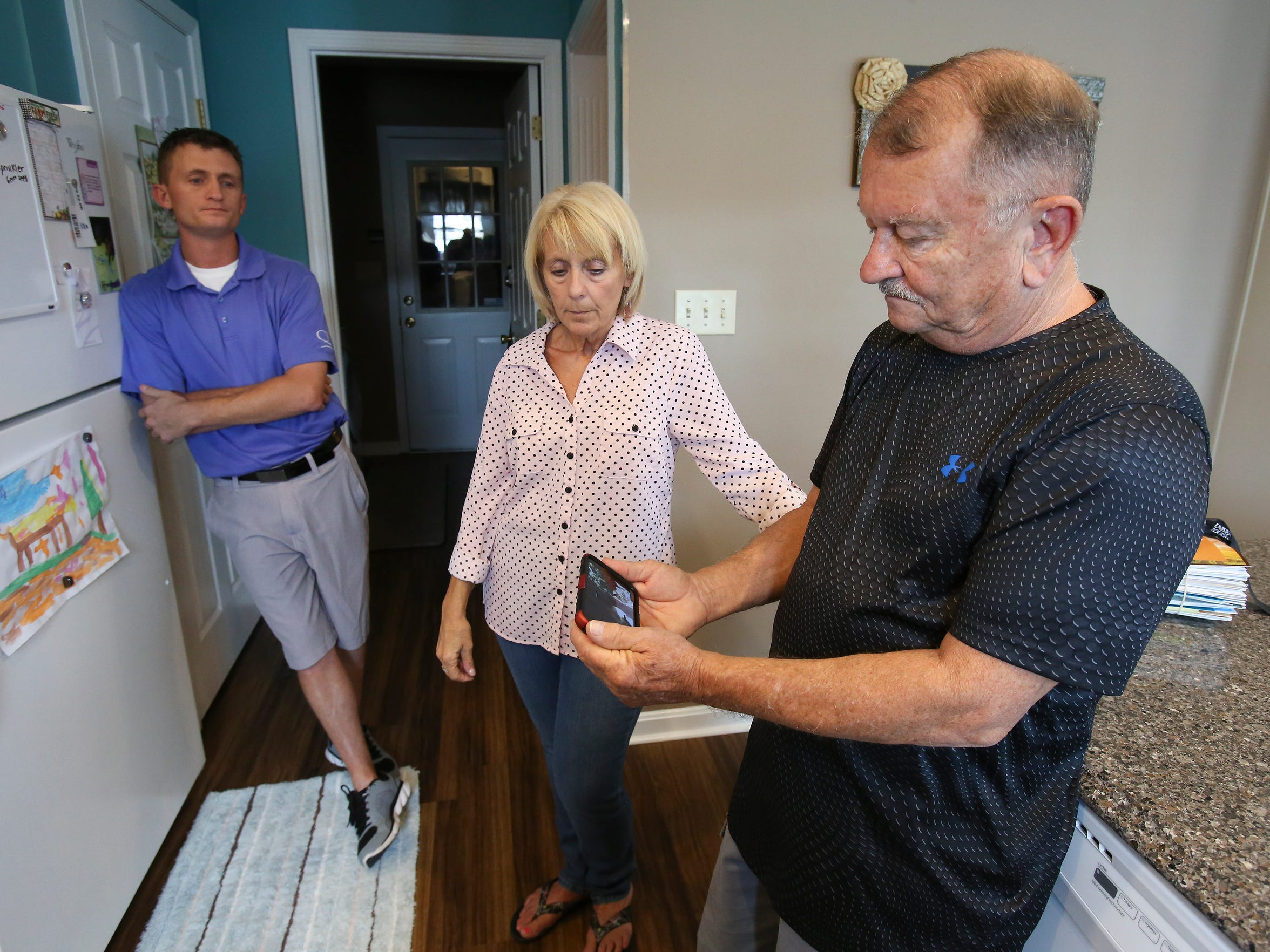 Karl Cooley, right, searches for audio recordings on his smartphone as his wife Brenda Cooley and son Aaron Cooley, 33, left, look on.  They were looking for recordings of their son Adam Cooley who died of a drug overdose. 