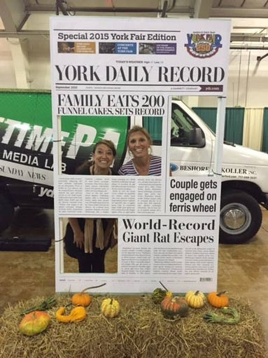 People enjoy posing with the York Daily Record front