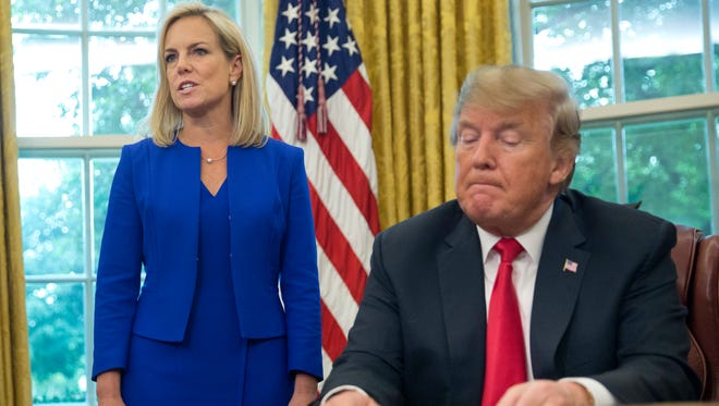 President Donald Trump, right, listens as Homeland Security Secretary Kirstjen Nielsen, left, addresses members of the media before Trump signs an executive order to end family separations at the border.