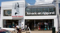 Passers-by walk down the street past the American Apparel