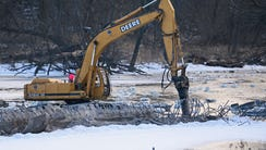 An MMSD contractor uses an excavator arm to break apart