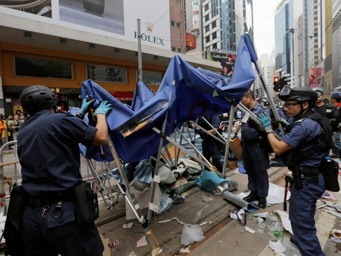 Police officers remove a tent from a road in the occupied