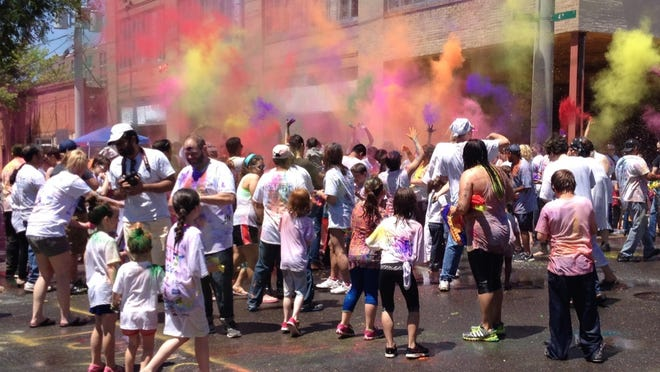 The streets and people in front of Tamp & Grind covered with colors during the 2014 Holi Fest celebration in downtown Alexandria.