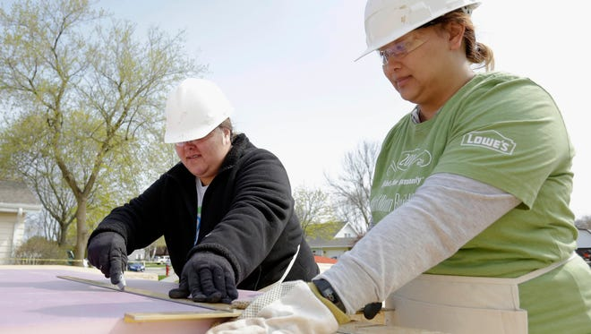 Future homeowner Katy Thao, left, measures insulation as Xue Yang holds the material at the North 11th Street Habitat for Humanity build Saturday, May 7, 2016 in Sheboygan.