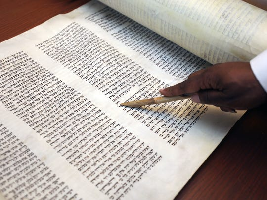 Rabbi Baruch A. Yehudah from the B'Nai Adath Kol Beth Yisrael congregation in Brooklyn, holds a pointer over a portion of the torah.