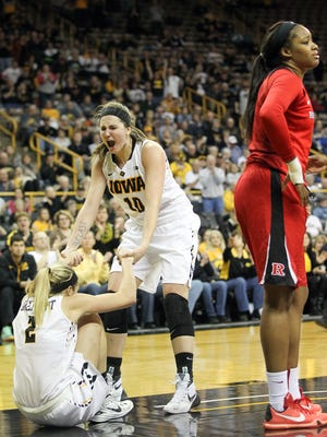Iowa's Ally Disterhoft gets help from Megan Gustafson after drawing a foul during the Hawkeyes' game against Rutgers at Carver-Hawkeye Arena on Monday, Jan. 4, 2016.