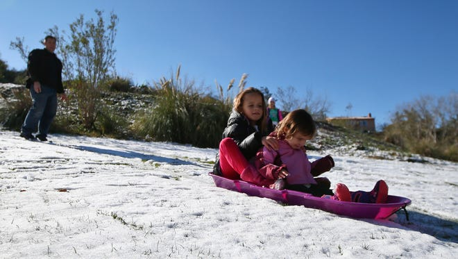 Ryanne Girard, 9, and her sister, Harper, 2, are stuck in the slush while they attempt to sled down a hill after a rare snow storm hits parts of Southern California Wednesday, Dec. 31, 2014, in Temecula, Calif.