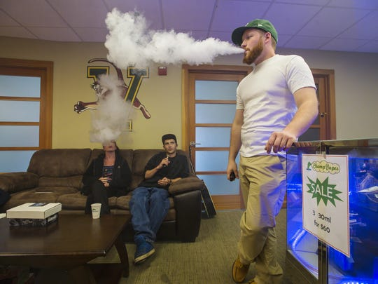 Leigh-Ann Dennean, from left, Kevin LaForce and Sean O'Hearn relax in the vape lounge at Champ Vapes in Burlington on Monday, May 9, 2016.