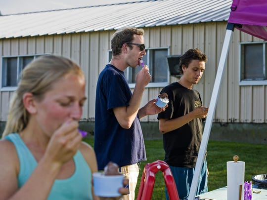 Spencer Needham of Burlington, center, licks his spoon at the pop-up gelato stand at Farr Farms in Richmond on Wednesday, July 27, 2016.