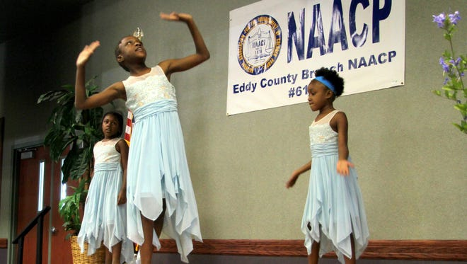 """From left, Apzara, 9, Acheizyah, 10, and Azjnarayi, 7, White perform a praise dance during the Juneteenth celebration. Their mother, Enid White, said the girls have learned about black history in the past year as she home schools them. """"We really wanted to show support for this,"""" she said."""
