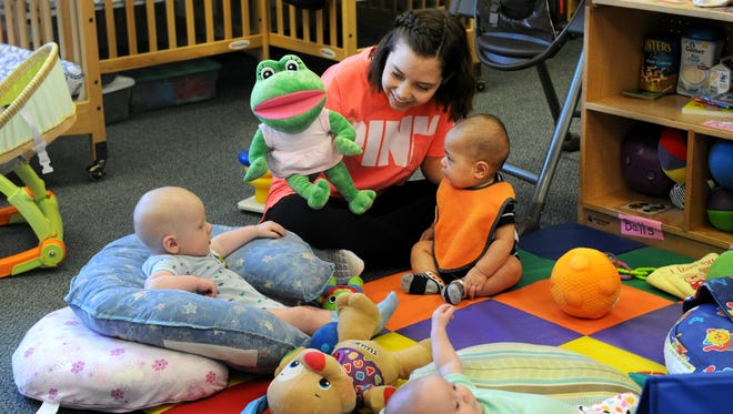 Aaliyah Garcia, from Abilene High School, interacts with babies at Day Nursery of Abilene Vine Street branch Thursday. Garcia is taking a child guidance class at school and the visits are part of the class.