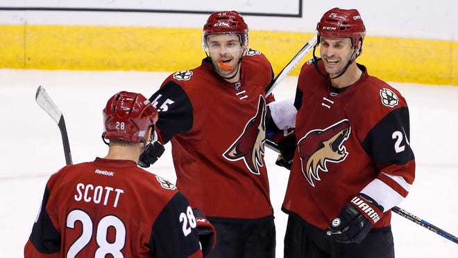 Arizona Coyotes' Stefan Elliott (45) celebrates his goal against the Edmonton Oilers with teammates John Scott (28) and Kyle Chipchura (24) during the second period of an NHL hockey game Thursday, Nov. 12, 2015, in Glendale, Ariz.