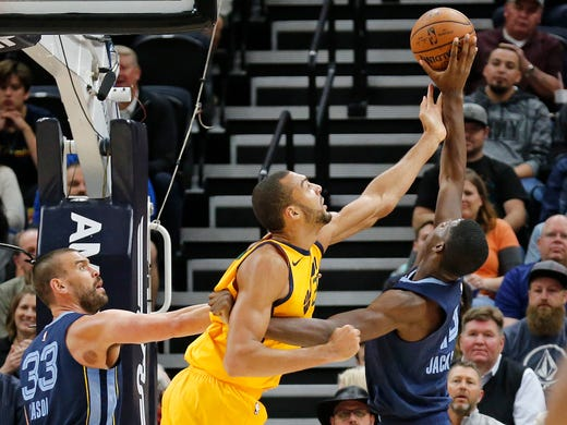 Utah Jazz center Rudy Gobert, center, battles for a rebound with Memphis Grizzlies' Jaren Jackson Jr., right, while Grizzlies' Marc Gasol (33) watches in the first half of an NBA basketball game Monday, Oct. 22, 2018, in Salt Lake City. (AP Photo/Rick Bowmer)