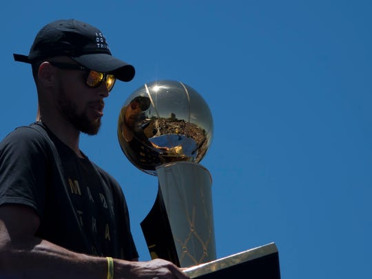 June 15, 2017; Oakland, CA, USA; Golden State Warriors guard Stephen Curry (30) holds the championship trophy during the Warriors 2017 championship victory parade in downtown Oakland.