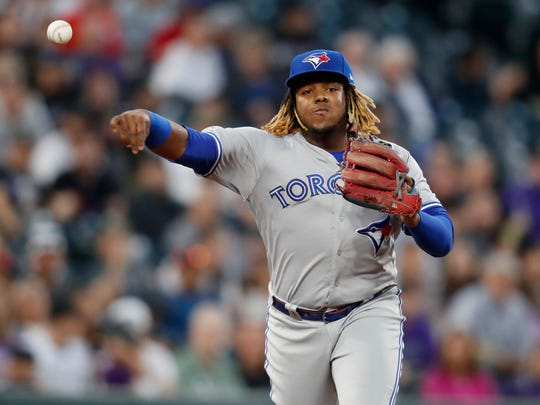 Toronto Blue Jays third baseman Vladimir Guerrero Jr. throws to first base to put out Colorado Rockies' Brendan Rodgers in the fourth inning of a baseball game Saturday, June 1, 2019, in Denver. (AP Photo/David Zalubowski)