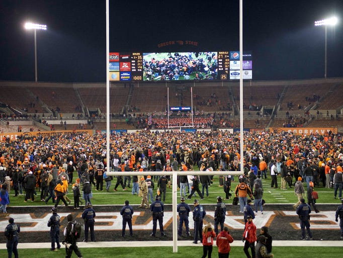 Oregon State football fans rush the field at the end