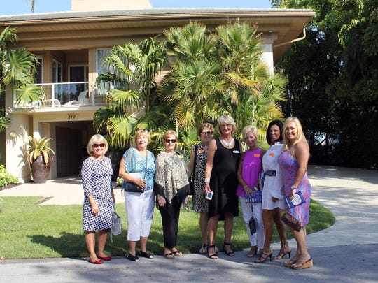 A group of tour participants enjoy a photo outside one of the homes.
