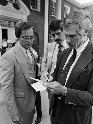 Ted Turner, right, goes over his notes with associates Ed Kessler, left, and Tom Wheeler prior to the start of the Cable News Network on June 1, 1980, in Atlanta. The 24-hour-a-day cable network began with a speech by Turner.