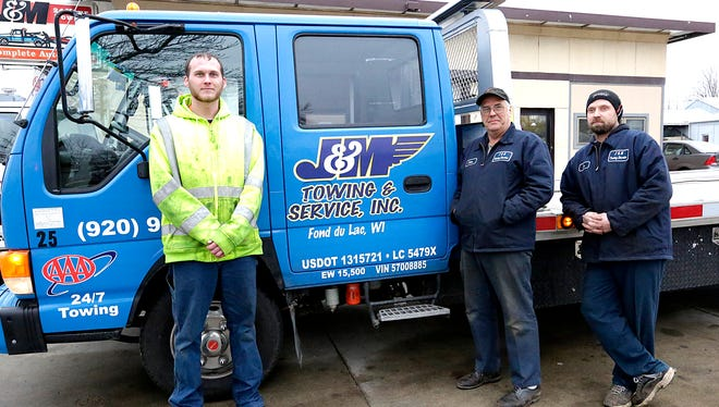 J&M Towing employee Mikel Chrysler, owner John Schmitz and employee Jimmy Wojkiewicz stand next to their new flatbed tow truck.