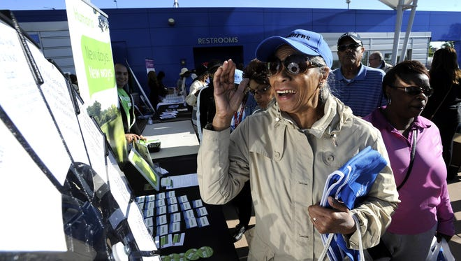 Darneice Rulledge, 72, of Detroit, correctly answers a health question at the Humana display and receives a gift.