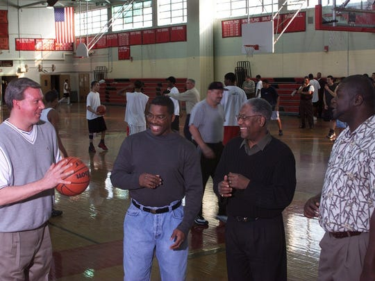 Members of the 1981 Neptune High School boys basketball State Championship team; (from left) Bob Braun, Terry Fisher, Coach Henry Moore and Carl Braggs gather 20 years after their state win to reminisce as the 2000-01 team practices in the background, getting ready for Camden.