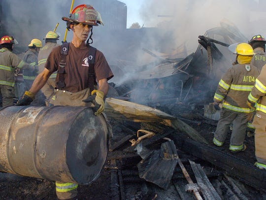 Firefighters work to put out a grass and barn fire Sunday near La. 103.