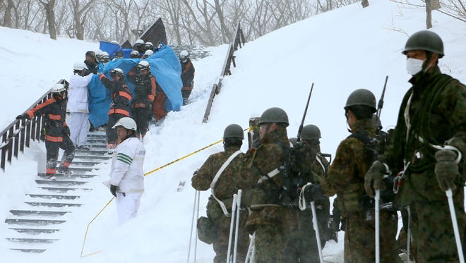 Firefighters carry a survivor they rescued from the site of an avalanche in Nasu town, Tochigi prefecture on March 27, 2017.