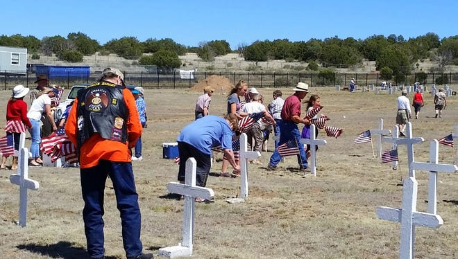 Volunteers came in all ages and for many different reasons to place flags on the graves of those buries at Fort Stanton's military cemetery.