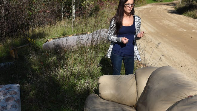 Duck Lake Road resident Amanda LaFord pauses by a pile of discarded furniture that's been dumped about 100 yards from her home. LaFord, who's lived along the Highland Township road for about a year, has watched as the dumping of old furniture continues.