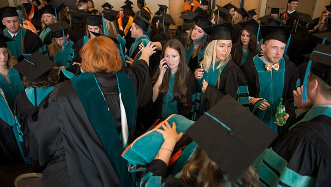 UTHSC graduates rush to hand out their graduation regalia at their ceremony in the Cook Convention Center in May 2017.