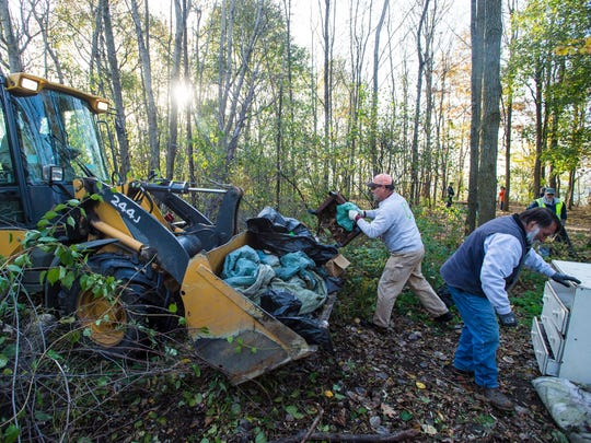 A crew from Burlington's Parks & Recreation and Publics Works departments clear a homeless campsite on city-owned land off North Avenue on Thursday, November 9, 2017.