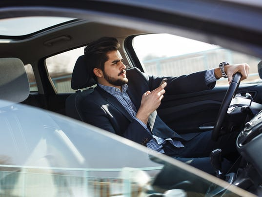 Handsome businessman texting message on the phone in car.